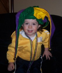 Olivia dressed in a jester hat and Mardi Gras beads.