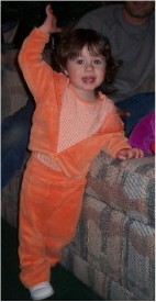Olivia in an orange outfit, waving.