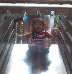 Olivia sliding down a playground slide.